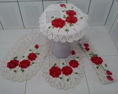 Jogo de banheiro com flores vermelhas.