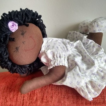 Boneca de pano negro deitada