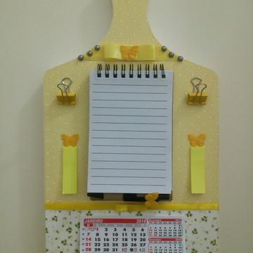 Tábua decorada com bloco e prendedor de papel e calendário