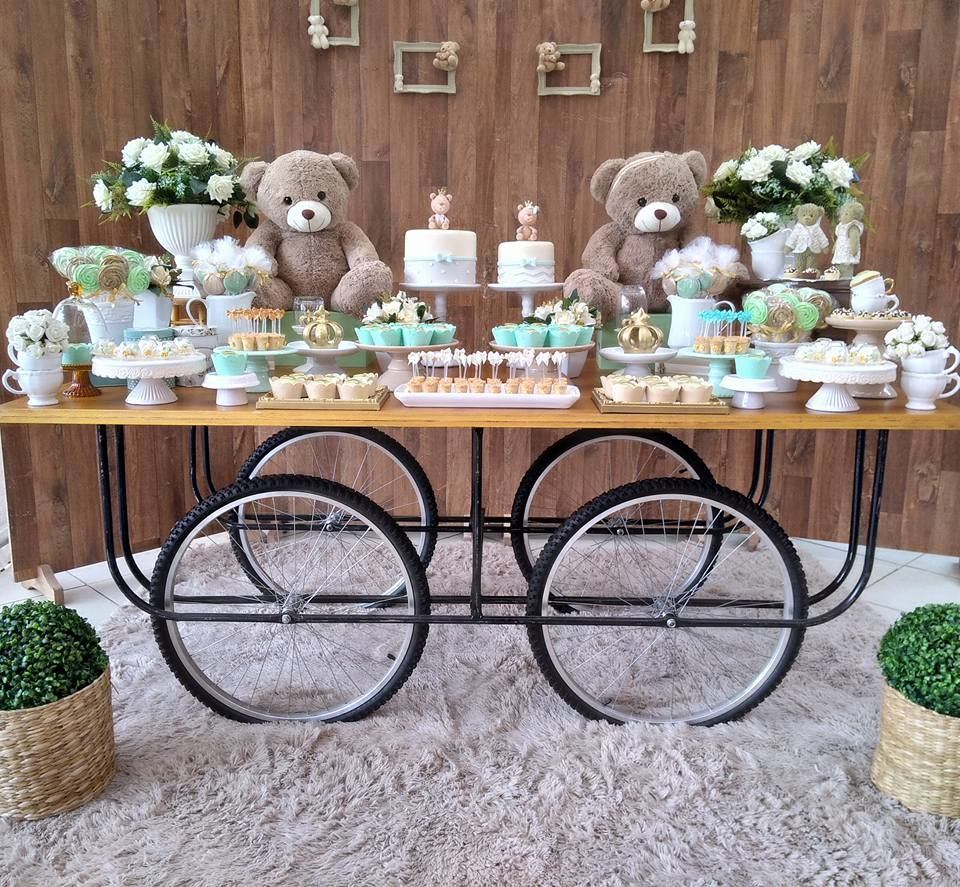 Decoração de chá de bebê gêmeos com painel rústico, mesa móvel, dois bolo e doces em dobro, além de ursinhos e jarros com plantas brancas